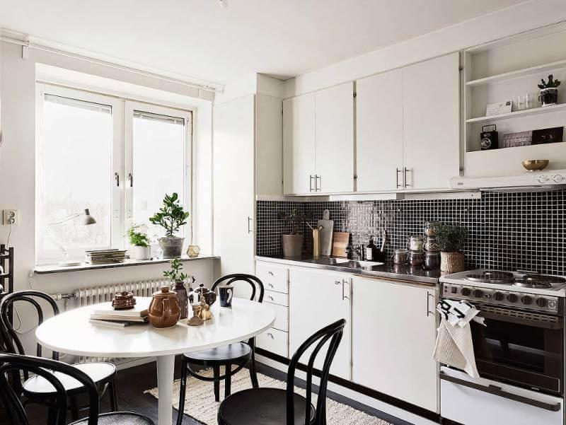 Малогабаритное пространство кухни за счет белого цвета визуально получило объем