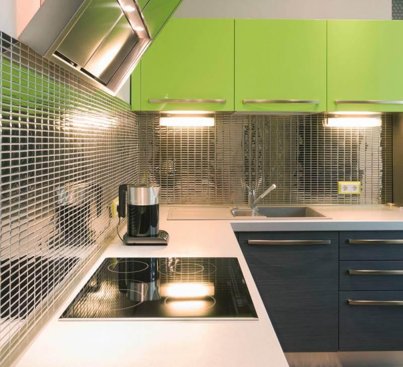 Мозаика с зеркальной поверхностью стала доминантной в интерьере П-образной кухни